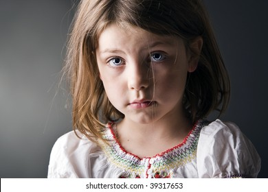 a dramatic low key image of a sad little girl looks out pensively