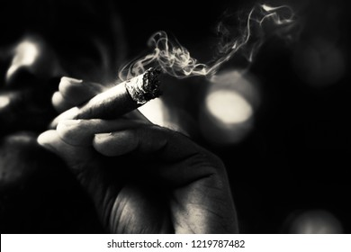 Dramatic low key portrait of a man with beard smoking cigar.The monochrome of a man smoking in dark shade with bokeh. Film stock color tone with grain.Selective focus
