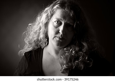 Dramatic Low Key Shot of a 30s Woman Looking at the Camera