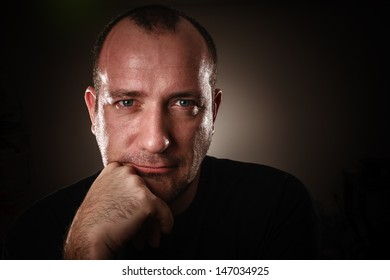 Dramatic low-key portrait of adult man looking in camera, closeup.