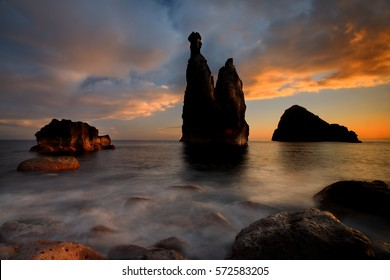 Dramatic Madeira seascape dawn. Long exposure from the rocky shore of the coast of Ribeira da Janela, Madeira island. Sunrise seascape, silhouette of two steep cliffs and misty rocks hit by waves