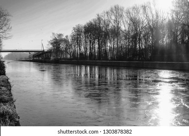 Dramatic and monochrome sunrise over a Beautiful early winter landscape with a frozen river or canal, treelined riverside and grass at sunrise creating a tranquile and quiet scenic nature background