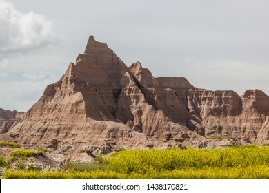 Dramatic mountain formations carved out by erosion showing layers of rocks with spring wildflowers below in Badlands National Park, South Dakota.