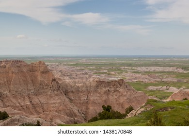 Dramatic mountain formations carved out by erosion showing layers of rocks with spring grass and distant flat prairie lands in Badlands National Park, South Dakota.