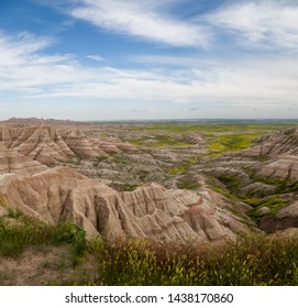 Dramatic mountain formations carved out by erosion showing layers of rocks with spring wildflowers in Badlands National Park, South Dakota.