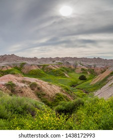 Dramatic mountain formations carved out by erosion showing layers of rocks with spring wildflowers and a stormy sky blocking the sun in Badlands National Park, South Dakota.