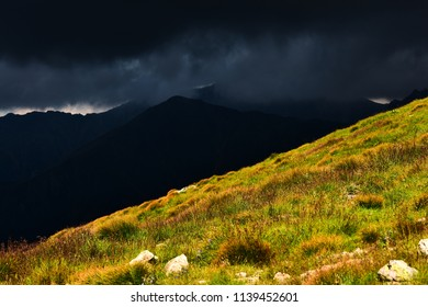 Dramatic mountainous landscape with dark, almost black stormy clouds and sunlit grassy hill.