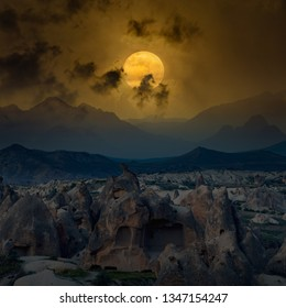 Dramatic mystical background - glowing full moon rises above mountains, dark scary clouds silhouettes in glowing sky. Elements of this image furnished by NASA