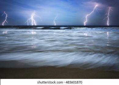 Dramatic nature background - lightnings in dark sky, stormy sea, big waves