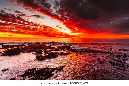 Dramatic nature landscape. Red sunset on the ocean shore. Beautiful sky. Shallow beach of the Pacific ocean