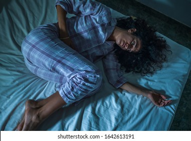 dramatic night lifestyle portrait of young sad and depressed middle eastern woman with curly hair sleepless in bed suffering excruciating period pain holding her belly in fetal position
