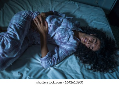 dramatic night lifestyle portrait of young sad and depressed latin woman with curly hair sleepless in bed suffering excruciating period pain holding her belly in fetal position