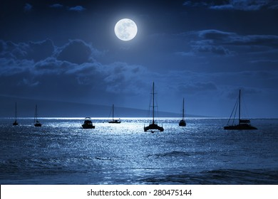 Dramatic night time photo illustration of a deep midnight blue sky with, bright full moon, over calm ocean waves in Maui, Hawaii.   Would make a great travel or vacation background.