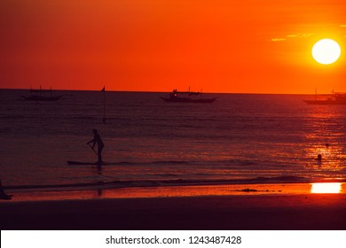 Dramatic orange sea sunset with boats. Summer time. Travel to Philippines. Luxury tropical vacation. Boracay paradise island. Seascape view. Tourism concept. Water transport. Paddle boarding