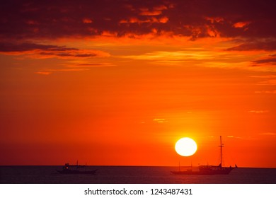 Dramatic orange sea sunset with boats. Summer time. Travel to Philippines. Luxury tropical vacation. Boracay paradise island. Nature background. Seascape, Tourism concept. Water transport. Copy space