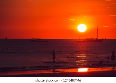 Dramatic orange sea sunset with boats. Summer time. Travel to Philippines. Luxury tropical vacation. Boracay paradise island. Seascape view. Tourism concept. Water transport. Man on SUP board