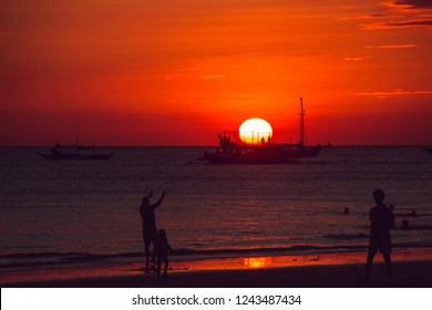 Dramatic orange sea sunset with sailboat and people silhouettes. Summer time. Travel to Philippines. Luxury tropical vacation. Boracay paradise island. Seascape view. Tourism concept. Water transport
