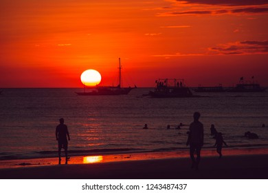 Dramatic orange sea sunset with sailboat. Summer time. Travel to Philippines. Luxury tropical vacation. Boracay paradise island. Nature background. Seascape view. Tourism concept. Beach people life