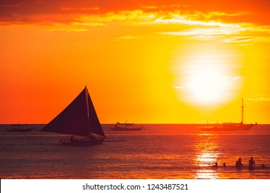 Dramatic orange sea sunset with sailboat. Summer time. Travel to Philippines. Luxury tropical vacation. Boracay paradise island. Nature background. Seascape view. Tourism concept. Water transport