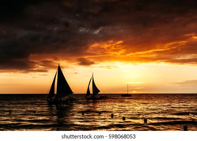 Dramatic orange sea sunset with sailboat in tropical country, clouds. Wide angle. silhouettes of boats, the solar disk. Philippines, Boracay