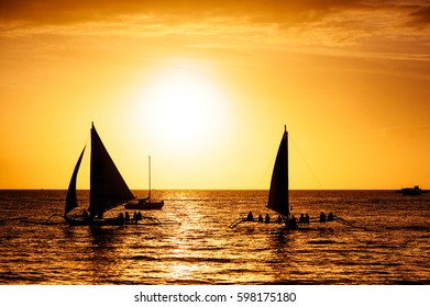 Dramatic orange sea sunset with two sailboats in tropical country, clouds. Wide angle. silhouettes of boats, the solar disk. Philippines, Boracay