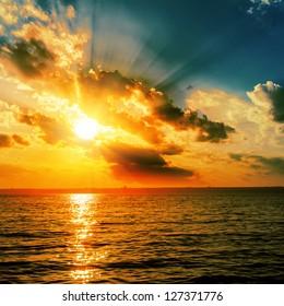 dramatic orange sunset over dark water