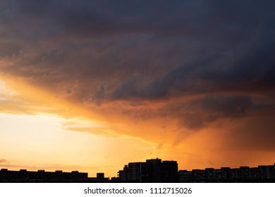 Dramatic orange sunset sky with massive clouds over buildings in Vilnius, Lithuania
