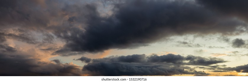 Dramatic Panoramic View of a cloudscape during a dark, rainy and colorful sunset. Taken in Alaska, USA.