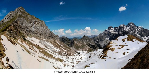 Dramatic panoramic view of a snow filled valley in the swiss alps as seen from the top of Fronalpstock mountain at Canton Glarus in Switzerland