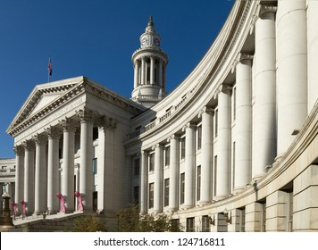Dramatic perspective of The City and County Building in Denver, Colorado, under a blue sky. The building is adorned with pink Breast Cancer Awareness ribbons.