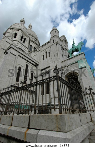 A dramatic perspective of the Sacre Coeur Cathedral against a cloudy blue sky.
