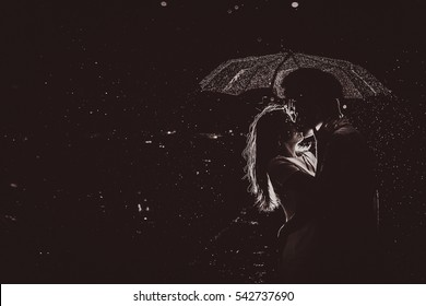 Dramatic photo of a bride and groom  in the night rain.