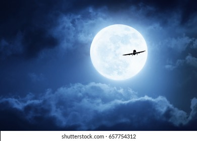 Dramatic photo illustration of a nighttime sky with brightly lit clouds and large, full, Blue Moon silhouetting a commercial aircraft .