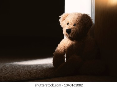 Dramatic photo of Teddy bear sitting on carpet in the dark room with sunlight shining from window, lowkey light shot of Lonely teddy sitting alone in living room international missing children's day