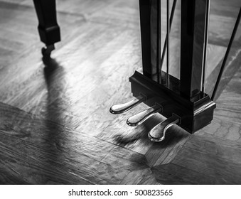 Dramatic piano foot pedals with soft reflection on a floor.