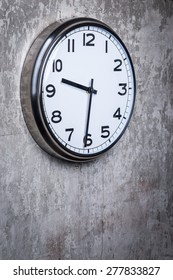 Dramatic picture of round wall clock hanging on the grey concrete wall