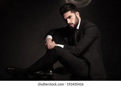 dramatic picture of a sexy young business man sitting on the floor