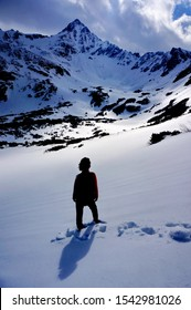 Dramatic picture of a woman standing under snowy mountain - High Tatras, Slovakia