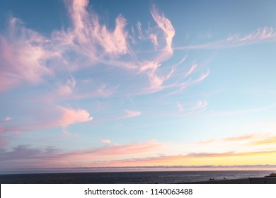 Dramatic pink, yellow, and blue sky during the sunset hour in Malibu California right off the Pacific Coast Highway. Palm trees in the foreground and beach houses.