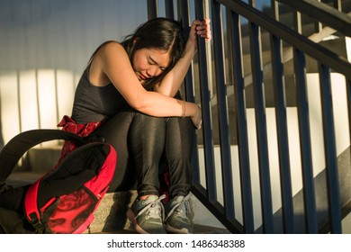 Dramatic portrait of Asian female college student bullied. Young depressed and sad Chinese girl sitting lonely on campus staircase suffering bullying and harassment feeling desperate and excluded