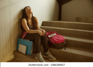 Dramatic portrait of Asian female college student bullied. Young depressed and sad Korean girl sitting lonely on campus staircase suffering bullying and harassment feeling desperate and excluded
