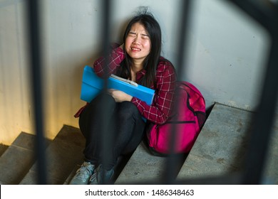 Dramatic portrait of Asian female college student bullied. Young depressed and sad Japanese girl sitting lonely on campus staircase suffering bullying and harassment feeling desperate and excluded