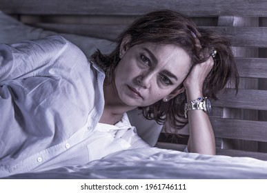dramatic portrait of attractive sad and depressed middle aged woman upset and lonely on bed suffering depression thoughtful and worried as mature lady through life crisis