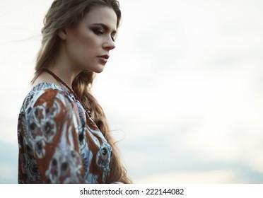 Dramatic portrait of beautiful hippie girl outdoors. Boho fashion style