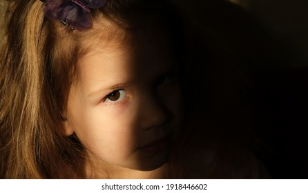 Dramatic  portrait of beautiful sad little child girl with shadow on face, close-up.  lonely in the dark. Childhood and problems of parents and children concept.