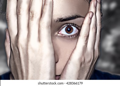 Dramatic portrait. Concept of anxiety and fear. Intense look through the hands covering the face.