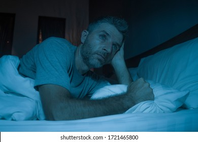 dramatic portrait in the dark of attractive depressed and worried man on bed suffering depression crisis and anxiety feeling lost lying sleepless in insomnia and life problem concept