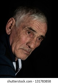 dramatic portrait of an elderly man on black background