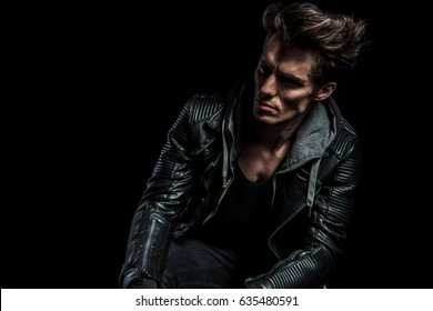 dramatic portrait of a fashion model in leather jacket looking away to a side on black backgroud