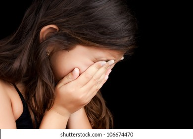 Dramatic portrait of a girl crying with her hands on her face isolated on a black background